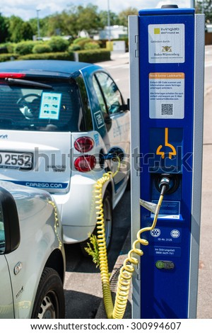 STUTTGART, GERMANY - JULY 25, 2015: An electric Smart of car sharing company car2go is being plugged into a charging station in Stuttgart, Germany. Car2go is a company of the Daimler group of - stock photo