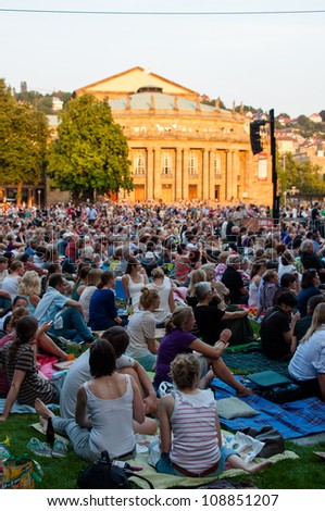 STUTTGART, GERMANY - JULY 25: More than 5.000 people are watching the public viewing of the premiere of Mozars opera Don Giovanni on a large screen in front of the Opera building in Stuttgart. - stock photo