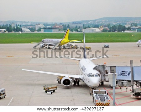 Stuttgart, Germany - May 21, 2008: Airport Stuttgart runway - passenger bridge leading to Lufthansa airplane. Several other aircrafts in the background. - stock photo