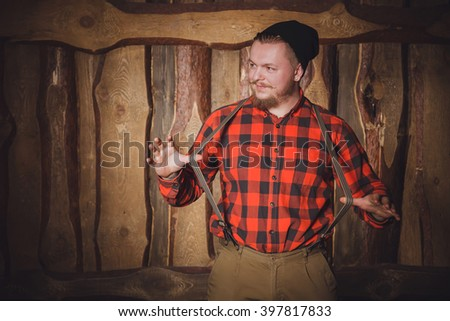 Style lumberjack. Woodcutter with a beard and mustache, wearing a red shirt, pants and suspenders with an ax on a wooden background. Modern style. Cheerful lumberjack - stock photo