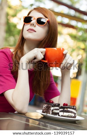 Style redhead girl with cup and cake sitting on the bench in the cafe - stock photo