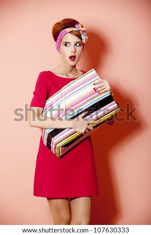 Style redhead girl with shopping box at pink background. - stock photo