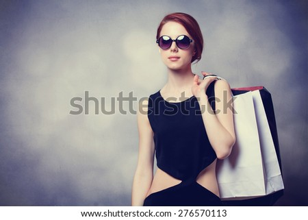 Style redhead girl with sunglasses and black dress with shopping bags on grey background - stock photo