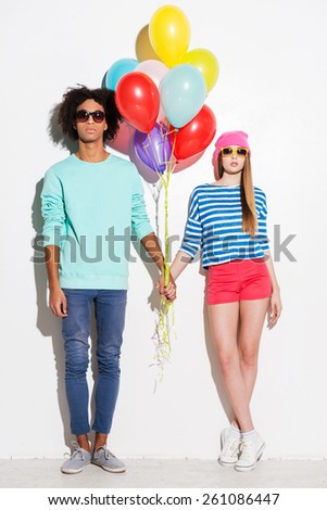 Style with the colorful attitude. Funky young couple holding balloons while standing against white background - stock photo