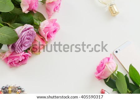 Styled desktop scene  with  mobile and flowers, copy space on white table - stock photo