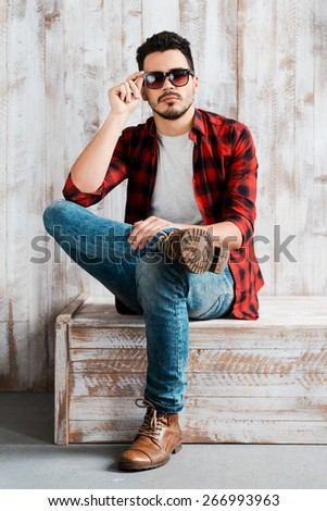 Stylish and confident. Handsome young man adjusting his sunglasses and looking at camera while sitting against the wooden wall  - stock photo