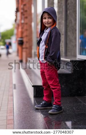 stylish baby boy having fun outside. Cute happy boy child outdoors. cute little stylish boy in urban style in the city. Happy child posing outdoor. - stock photo