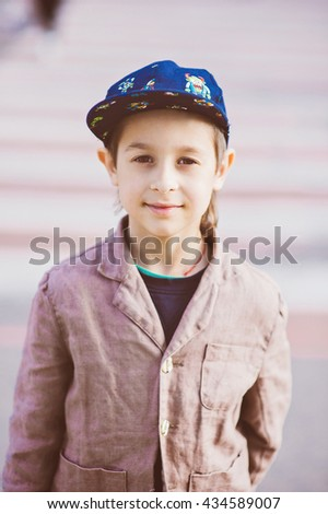 Stylish baby boy having fun outside in the city. Cute happy boy child outdoors, little stylish boy in classic style in the city. Happy child posing outdoor.Sunset time. - stock photo