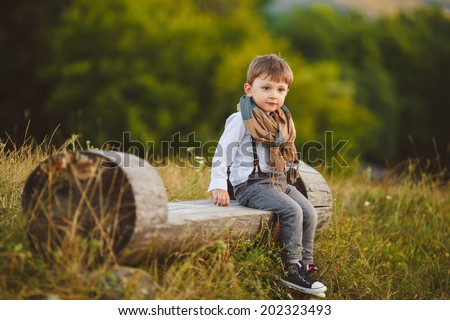 stylish baby boy having fun outside in the park. Cute happy boy child outdoors - stock photo
