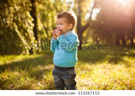 stylish baby boy having fun outside in the park,eating apple - stock photo