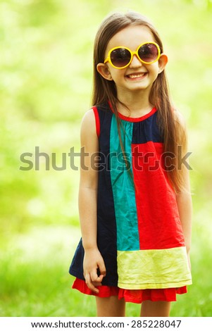 Stylish baby girl with light brown hair in trendy sunglasses and avant-garde style dress standing in the park and smiling. Hipster style. Sunny weather. Copy-space. Outdoor shot - stock photo