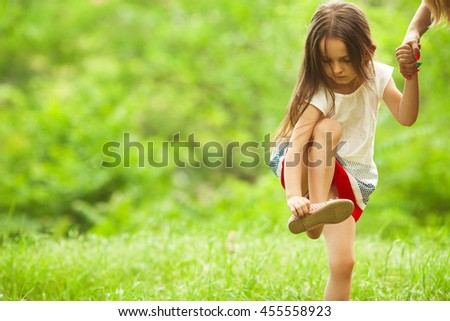 Stylish baby girl with long light brown hair in trendy vintage red and white dress standing in the park and trying to put on a shoe. Sunny weather. Copy-space. Outdoor shot - stock photo