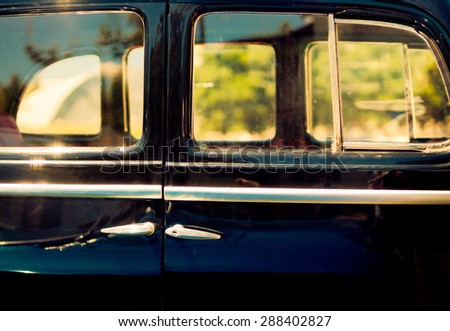 Stylish background of the old automobile with door handles and window frames. Retro car in vintage style at sunset light. Oldtimer black automobile, side view.  - stock photo