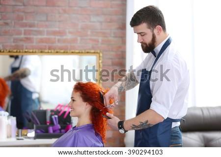 Stylish barber making new haircut - stock photo
