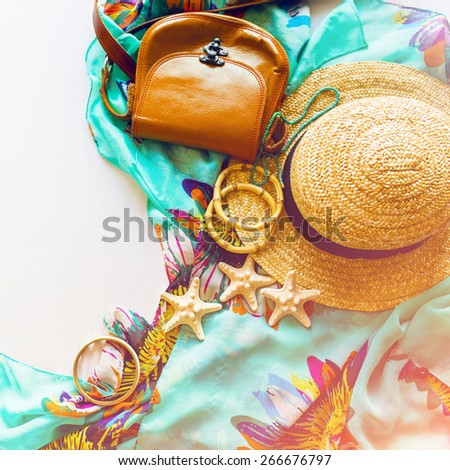Stylish beach accessories . Straw hat , little leather  bag and a lot of bamboo bracelets . Summer lifestyle. Bright colors. Vacation mood. - stock photo