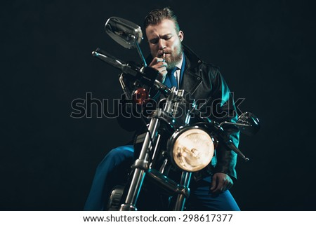 Stylish bearded man in a formal suit sitting on a bike lighting up a cigarette in the darkness as he waits for someone with the headlight shining in the darkness - stock photo
