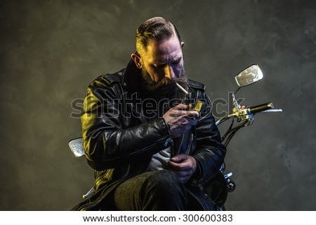 Stylish Bearded Man in Black Leather Jacket and Jeans Lighting a Cigarette While Sitting on his Motorcycle Against Smoky Background. - stock photo