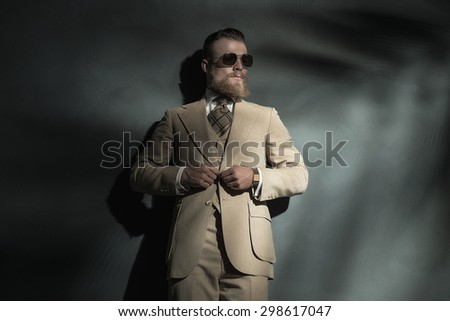 Stylish bearded man wearing trendy sunglasses standing leaning against a wall buttoning his jacket and looking towards a beam of light on the right of the frame - stock photo