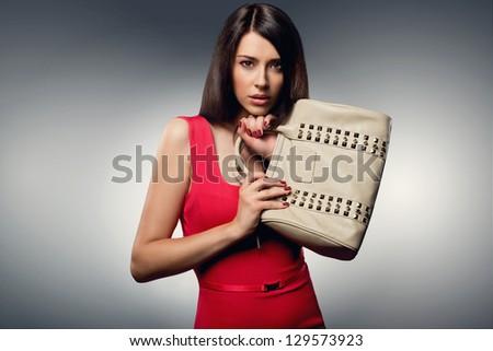 Stylish beautiful brunette woman wearing red dress holding nice handbag. Fashion picture - stock photo
