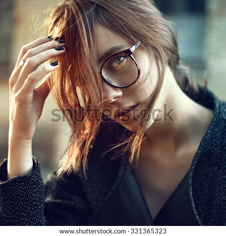 Stylish beautiful girl in fashionable glasses closeup on a sunny day - stock photo