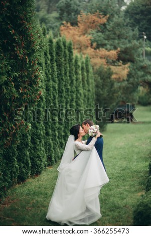 Stylish beautiful happy wedding couple kissing and embracing in Botanical Garden - stock photo