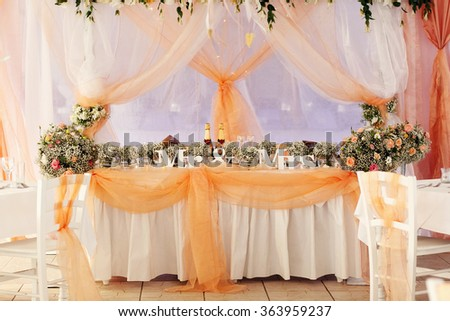 Stylish beautiful luxury wedding decor with a lot of flowers on the tables in restaurant hall - stock photo