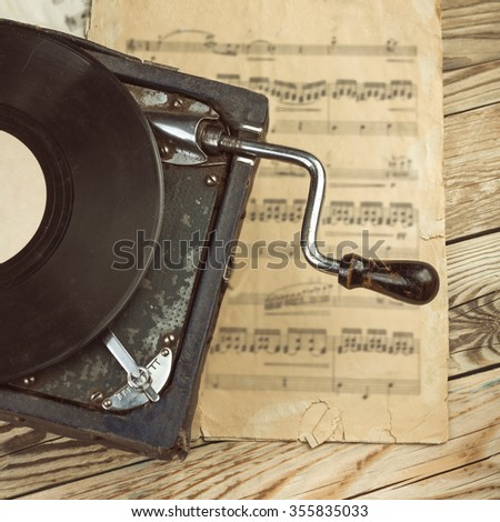 Stylish beautiful old gramophone with manual winding on a wooden table. Musical notes. Top view.  Toned filtered square photo  instagram retro vintage style - stock photo