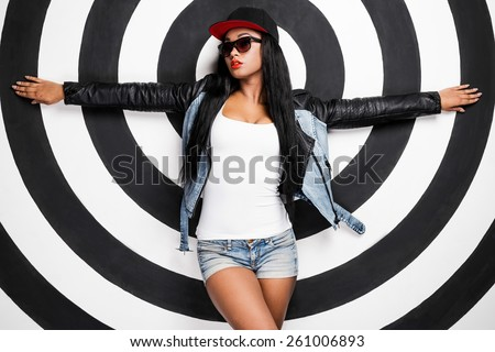 Stylish beauty. Attractive young African woman adjusting her cap while posing against black and white  background - stock photo
