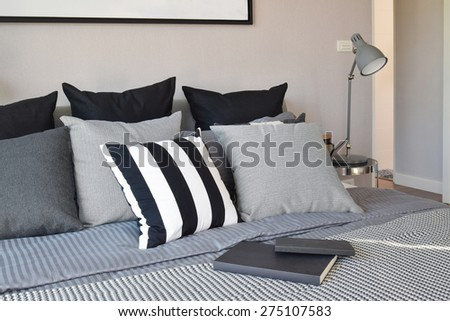stylish bedroom interior design with black patterned pillows on bed and decorative table lamp. - stock photo