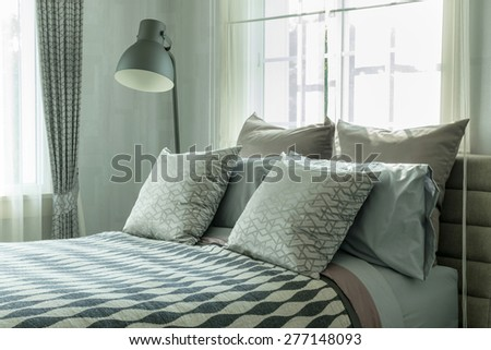 stylish bedroom interior design with patterned pillows on bed and decorative table lamp. - stock photo