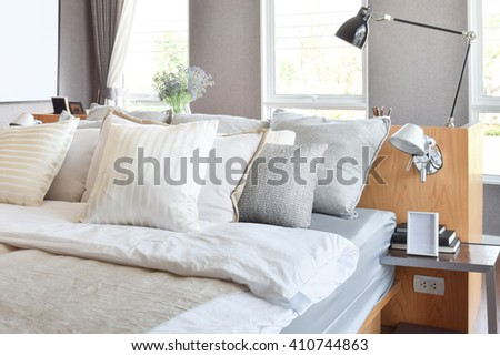 stylish bedroom interior design with white striped pillows on bed and decorative table lamp. - stock photo