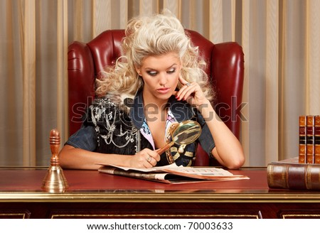 stylish blond reading newspaper using magnifying glass at the wooden desk - stock photo