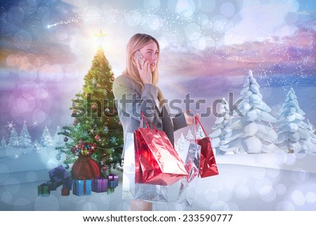 Stylish blonde holding shopping bags against snowy landscape with fir trees - stock photo
