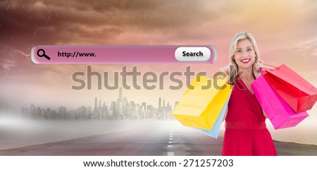 Stylish blonde in red dress holding shopping bags against large city on the horizon - stock photo