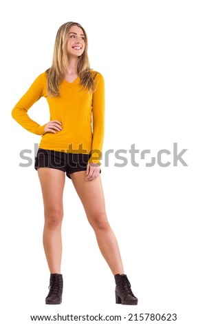 Stylish blonde smiling with hand on hip on white background - stock photo