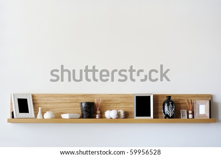 Stylish bookshelf on a white wall - stock photo