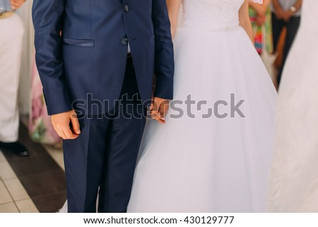 Stylish bride and groom at their wedding holding hands - stock photo