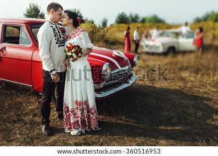 stylish bride and happy groom near car on the background of nature and friends bridesmaids - stock photo