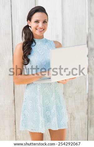 Stylish brunette using a laptop against bleached wooden fence - stock photo