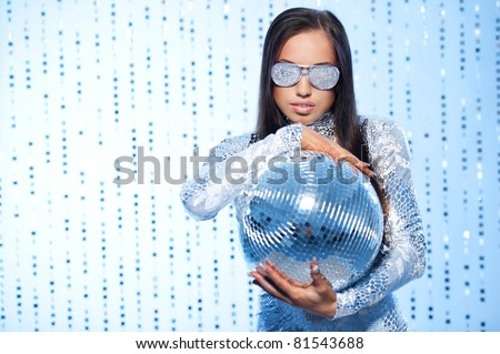 Stylish brunette with a disco ball - stock photo