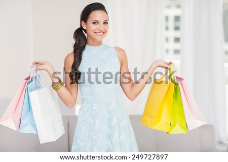 Stylish brunette with shopping bags at home in the living room - stock photo