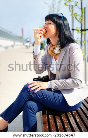 Stylish brunette woman eating an apple in the park, eating healthy and smiling - stock photo