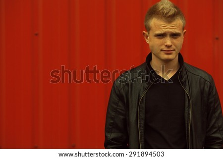 Stylish bully concept. Portrait of brutal young man with short blond hair wearing black jacket and posing over red urban background. Hipster style. Close up. Copy-space. Outdoor shot - stock photo