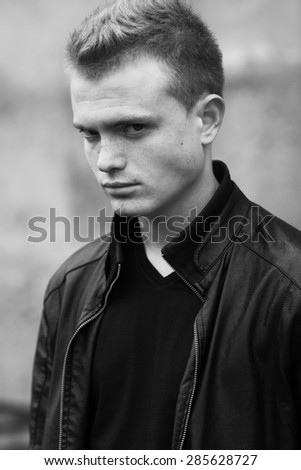 Stylish bully concept. Portrait of brutal young man with short wet hair wearing black jacket and posing over urban background. Hipster style. Close up. Black and white outdoor shot - stock photo
