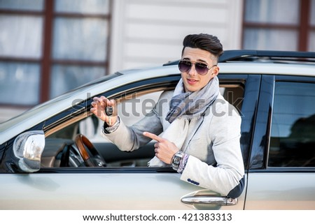 Stylish businessman in the window of his own luxury car. Cheerful and joyful. Show key from his car - stock photo