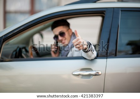 Stylish businessman in the window of his own luxury car. Cheerful and joyful. Show thumb  - stock photo