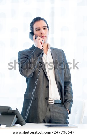 Stylish businessman standing talking on a land line phone in his office listening to the conversation in a relaxed stance with his hand in his pocket. - stock photo
