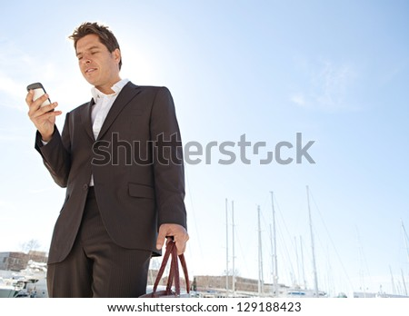 "Stylish businessman using his ""smart phone"" while standing near a marine with luxury yachts against a deep blue sky and sea. - stock photo"