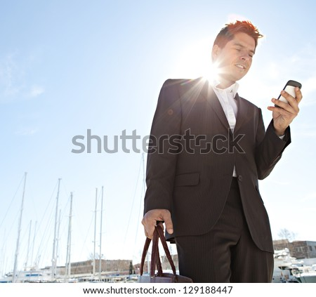 "Stylish businessman using his ""smart phone"" while standing near a marine with luxury yachts against a deep blue sky and sea with the sun filtering through his neck. - stock photo"