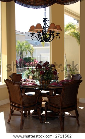 stylish casual dining table with place settings in upscale home - stock photo
